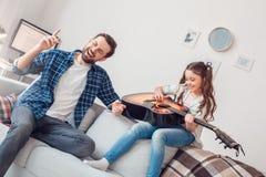 Vater und wenig Tochter zu Hause, die den Vater singt das frohe Weilemädchen spielt Gitarre sitzt lizenzfreie stockfotografie