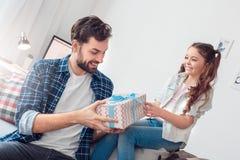 Vater und wenig Tochter zu Hause, die Mannholdinggeschenk von der Tochter überrascht sitzt lizenzfreie stockbilder
