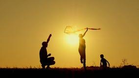 Vater und zwei Kinder, die mit einem Drachen in der Natur spielen Die Einheit der Familie und Erholung der im Freien stock video