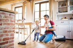 Vater und zwei Kleinkinder, die Hausarbeit tun lizenzfreie stockfotos