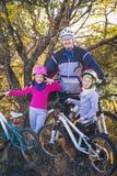 Vater und zwei Töchter auf Fahrrädern im Herbst lizenzfreies stockfoto