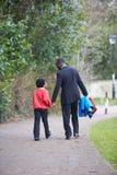 Vater-Walking Son To-Schule entlang Weg Stockfoto