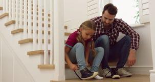 Vater, welche ihrer Tochter hilft, Schuhe auf Treppe in einem behaglichen Haus 4k zu tragen stock video