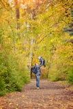 Vater wirft einen kleinen Sohn Bäume, die noch mit etwas goldenen Farben grün bleiben Weicher Fokus stockbilder