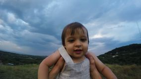 Vater wirft oben und dreht seinen Sohn auf dem Berg am Abend stock footage