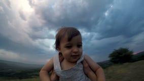 Vater wirft oben und dreht seinen Sohn auf dem Berg am Abend stock video footage