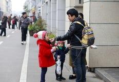 Vater zieht seine Tochter ein, um Snäcke, luftgetrockneten Ziegelstein rgb zu essen Lizenzfreie Stockfotos