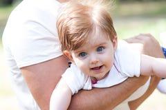 Vatergriffe auf Händen seiner Tochter lizenzfreies stockbild