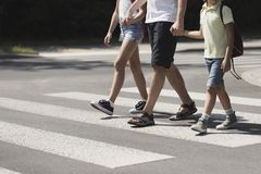 Vaterhändchenhalten mit seinen Kindern während auf Fußgängerübergang stockfotografie