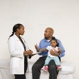 Vaterholdingschätzchen, das mit Kinderarzt spricht. Stockfoto
