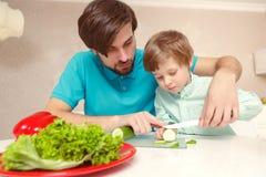 Vaterköche mit seinem Sohn lizenzfreie stockbilder