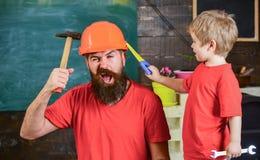 Vaterschaftskonzept Bringen Sie hervor, erziehen Sie mit Bart im Schutzhelm, der kleinen Sohn unterrichtet, verschiedene Werkzeug stockfoto