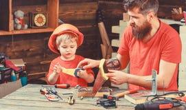Vaterschaftskonzept Junge, Kind beschäftigt im Schutzhelm lernend, Handsaw mit Vati zu benutzen Vater, Elternteil mit Bart lizenzfreie stockfotos