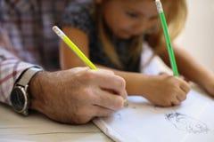 Vaterschreiben mit seiner Tochter Lizenzfreie Stockbilder