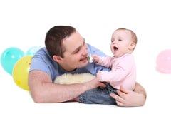 Vaterspiele mit der acht-Monatstochter. Lizenzfreie Stockfotos