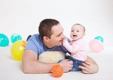 Vaterspiele mit der acht-Monatstochter Lizenzfreie Stockfotografie