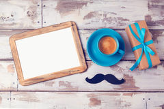 Vatertagshintergrund mit Fotorahmen, Kaffeetasse und Geschenkbox auf Holztisch Ansicht von oben Stockbild