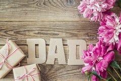 Vatertagshintergrund mit Pappbuchstaben, purpurrote Pfingstrosen a stockbilder