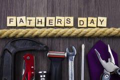 Vatertagsmitteilung auf einem hölzernen Hintergrund mit dem Satz Werkzeugen und Bindungen, getrennt durch Seil lizenzfreies stockbild