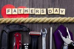 Vatertagsmitteilung auf einem hölzernen Hintergrund mit dem Satz Werkzeugen und Bindungen, getrennt durch Seil stockbilder
