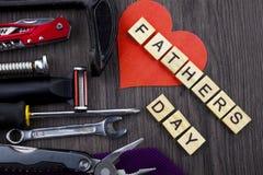 Vatertagsmitteilung auf einem hölzernen Hintergrund mit dem Satz Werkzeugen und Bindungen, getrennt durch Seil stockfotografie