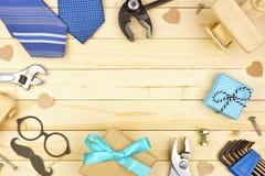 Vatertagsrahmen von Geschenken, von Bindungen, von Werkzeugen und von Dekor auf einem Naturholzhintergrund stockfotografie