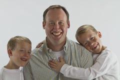 Vatertagsumarmung von 6 Jahren alten Zwillingen Stockfotografie