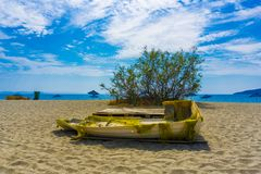 Vathi beach with blue crystal waters in eastern Mani region of Peloponnese, Greece. An old broken yellow fishing boat at Vathi beach with blue crystal waters in stock image