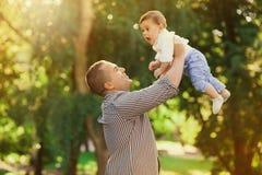 Vati, der aktive Spiele mit seinem Sohn draußen spielt Stockbild
