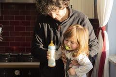Vati, der Baby in Hochstuhl einsetzt, nachdem ihre Milchflasche vorbereitet worden ist lizenzfreie stockbilder