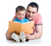 Vati, der ein Buch liest, um zu scherzen Lizenzfreie Stockbilder