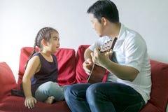 Vati, der Gitarre und ein Lied mit einem Mädchen spielt lizenzfreie stockfotografie