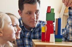 Vati, der mit Blöcken mit Kindern spielt stockfotos