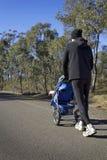 Vati, der mit Kinderwagen auf einer Landstraße rüttelt Lizenzfreies Stockbild