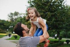 Vati, der mit seiner Tochter im Park spielt Stockfotos