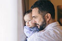 Vati, der sein Baby mit Neigung erzieht Stockfotografie