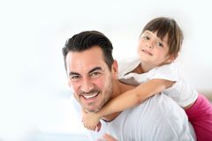 Vati, der sein kleines Mädchen auf seinem zurückbringt Lizenzfreie Stockfotos