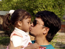 Vati, der seine Tochter küßt stockfotografie