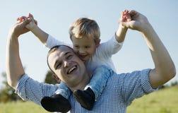 Vati, der seinem jungen Sohn eine Doppelpolfahrt gibt Stockfoto