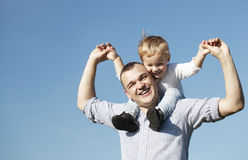 Vati, der seinem jungen Sohn eine Doppelpolfahrt gibt Lizenzfreie Stockbilder