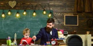 Vati, der seinem reizenden Jungen beibringt, wie man malt Sohn, der seine Vatimalerei aufpasst Kunstunterricht zu Hause Stockfoto