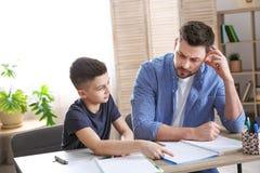 Vati, der seinem Sohn mit Hausarbeit hilft lizenzfreie stockbilder