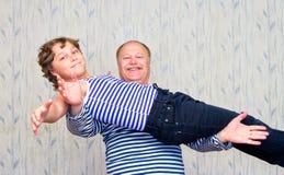 Vati, der seinen Sohn auf seinen ausgestreckten Händen hält Stockfotos