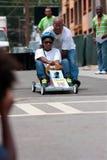 Vati drückt Tochter im Atlanta-Seifen-Kasten Derby Race Stockfotografie