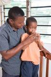 Vati gibt seinem Kind Wasser zum Getränk stockbilder