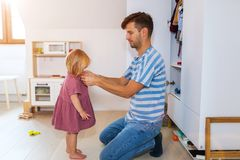 Vati hilft Kleinkindtochter, angekleidet zu erhalten lizenzfreies stockbild