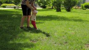 Vati hilft seiner Tochter, den ersten Schritt im Park auf dem Gras zu unternehmen stock video