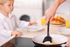 Vati macht Omelette für seinen Sohn und selbst Stockbild