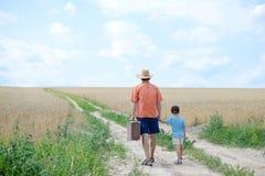 Vati mit dem Koffer, der seinen eigenhändig gehenden Sohn hält Stockbild
