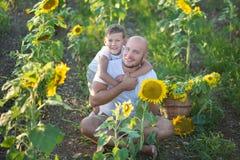 Vati mit dem Sohn, der auf einem Gebiet von Sonnenblumen umarmt Sohnumarmung sein Vater auf einem Gebiet von Sonnenblumen lizenzfreie stockfotos